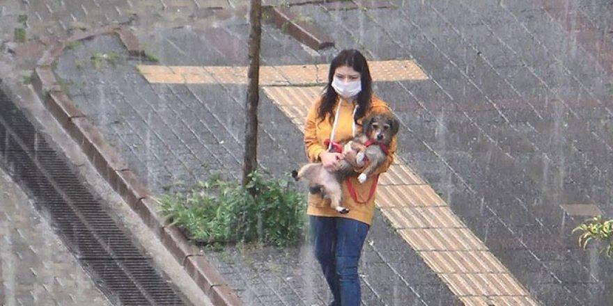 Şiddetli yağışa hazırlıksız yakalanınca köpeğini kucaklayıp koştu